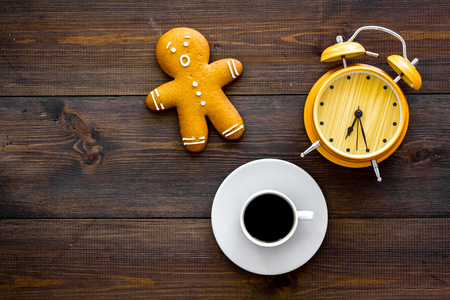 Time loss concept. Gingerbread man near alarm clock on dark wooden background top view space for text Stock Photo