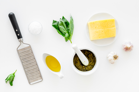 Ingredients for pesto sauce. Cheese, garlic, green basil, olive oil, salt near grater and mortar on white background top view Stockfoto