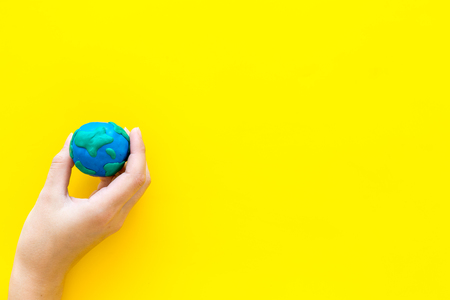 Earth. Hand hold plastiline symbol of planet Earth globe on yellow background top view space for text