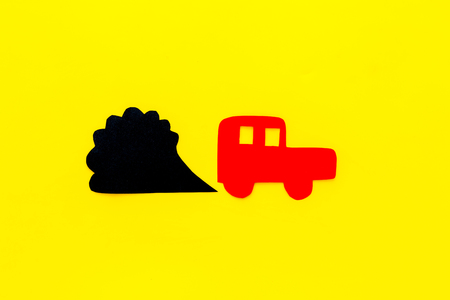 Car emitting dirty smoke. Pollution concept. Car and smoke cutout on yellow background top view copy space Stock Photo