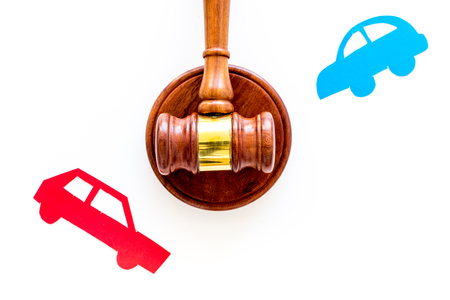 Car accident lawsuit concept. Two collided cars near judge gavel on white background top view copy space