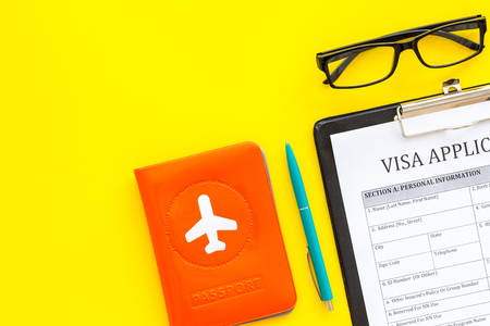 Fill visa application form. Form near glasses, pen, passport cover with airplane sign on yellow background top view space for text Фото со стока