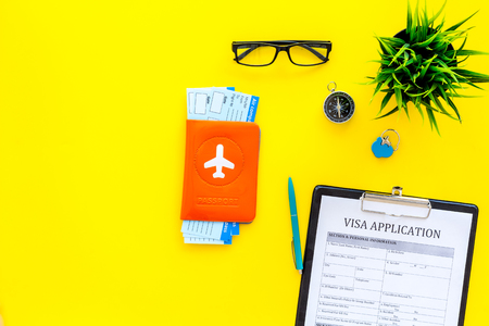 Prepare to trip. Do visa. Airplane tickets near passport cover with airplane silhouette, visa application form, compas on yellow background top view copy space Archivio Fotografico - 104352224