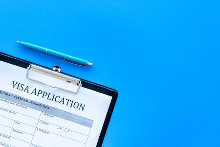 Visa prosessing. Registration of visas. Visa application form and pen on blue background top view copy space Stock Photo