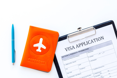 Documents for travel abroad. Visa application form, pen, passport cover with airplane silhouette on white background top view copy space