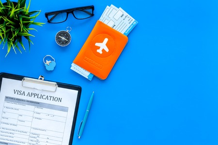 Planning vacation. Visa prosessing. Airplane tickets near passport cover with airplane silhouette, visa application form, compas on blue background top view copy space Archivio Fotografico - 104352235