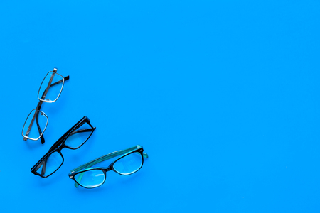 Glasses concept. Set of glasses with different eyeglass frame and transparent lenses on blue background top view copy space