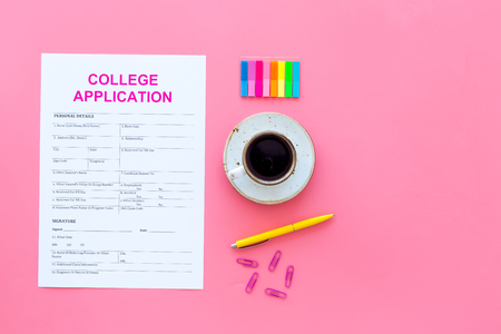 Apply college. Empty college application form near coffee cup and stationery on pink background top view copy space 스톡 콘텐츠
