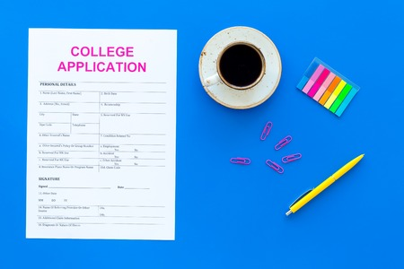 Higher education. College application form ready to fill near coffee cup and stationery on blue background top view Stock fotó