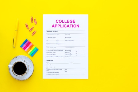 Apply college. Empty college application form near coffee cup and stationery on yellow background top view copy space