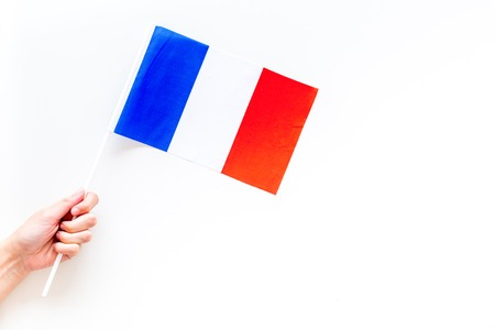 French flag concept. Hand hold small flag on white background top view copy space Stok Fotoğraf