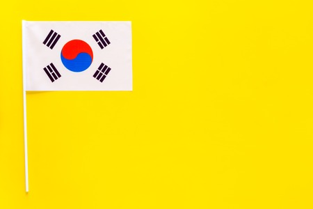 Korean flag concept. small flag on yellow background top view copy space
