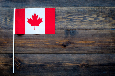 Canadian flag concept. small flag on dark wooden background top view copy space 스톡 콘텐츠