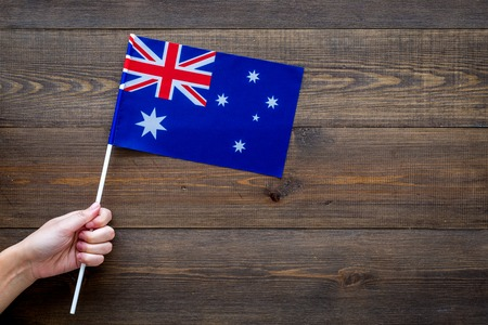 Australian flag concept. Hand hold small flag on dark wooden background top view copy space