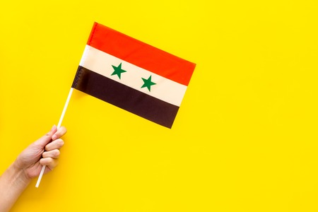 Syrian flag concept. Hand hold small flag on yellow background top view copy space