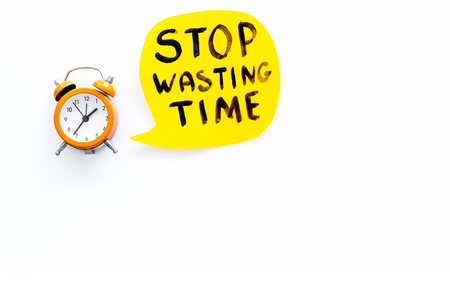 Stop wasting time hand letterng near alarm clock on white background top view copy space. Business concept, motivation. Banco de Imagens - 104398810