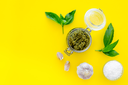 Green pesto sauce in glass jar near basil leaves and garlic on yellow background top view.