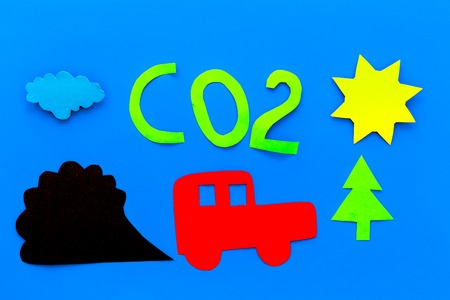 Cars emitting carbon dioxide. Pollution concept. harm the environment. Car and smoke cutout on blue background top view.