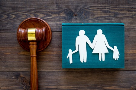 Family law, family right concept. Child-custody concept. Family with children cutout near court gavel on dark wooden background top view.