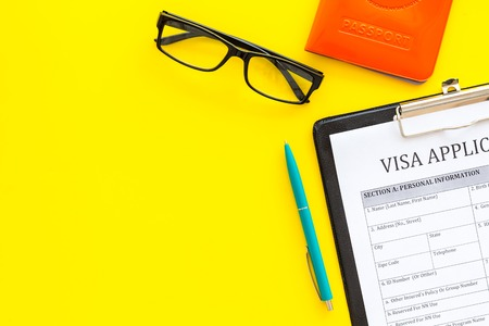Fill visa application form. Form near glasses, pen, passport cover with airplane sign on yellow background top view.