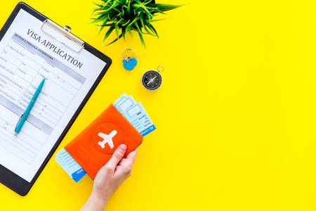 Planning vacation. Visa prosessing. Hand hold airplane tickets in passport cover with airplane silhouette near visa application form, compas on yellow background top view copy space 写真素材