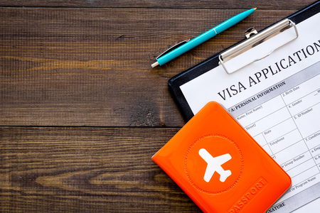 Visa prosessing. Registration of visas. Visa application form, pen, passport cover with airplane silhouette on dark wooden background top view copy space Фото со стока