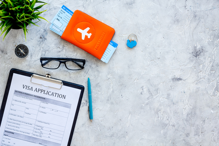 Planning vacation. Visa prosessing. Airplane tickets near passport cover with airplane silhouette, visa application form, compas on grey background top view copy space