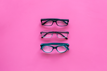 Glasses concept. Set of glasses with different eyeglass frame and transparent lenses on pink background top view copy space pattern