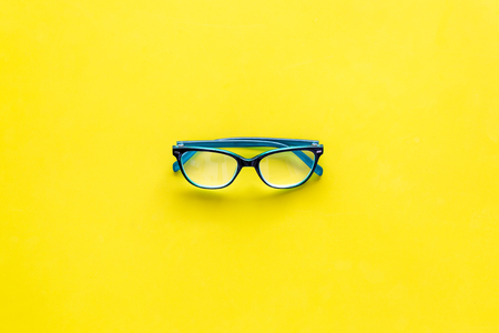 One glasses with transparent lenses on yellow background top view copy space