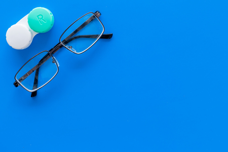 Way to improve vision. Contact lenses in container near glasses on blue background top view. Stock Photo