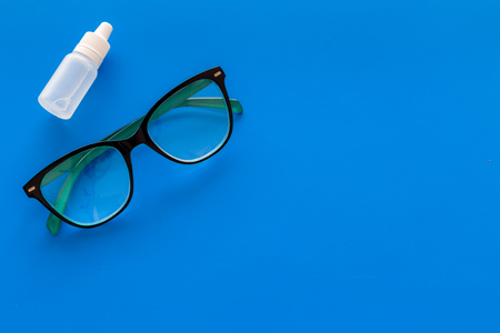 Eye drops in small bottle near glasses on blue background top view.