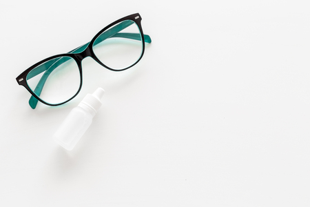 Eye drops in small bottle near glasses on white background top view.
