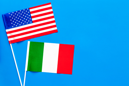 USA-Italia relations. Country cooperation. American and Italian flags on blue background top view copy space