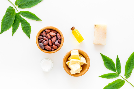 Natural organic cosmetics based on cocoa butter. Cocoa beans and cocoa butter, soap, cream, oil or lotion in small bottles on white background top view space for text Stock Photo