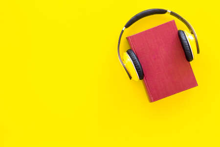 Audiobooks concept. Headphones put over hardback book with empty cover on yellow background top view.