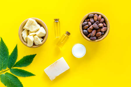 Cosmetics with cocoa butter for skin care. Cocoa beans and cocoa butter in bowl, soap, oil or lotion in small bottles on yellow background top view.