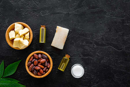 Cosmetics with cocoa butter for skin care. Cocoa beans and cocoa butter in bowl, soap, oil or lotion in small bottles on black background top view.