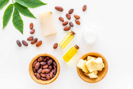 Cosmétique biologique naturelle à base de beurre de cacao. Fèves de cacao et beurre de cacao, savon, crème, huile ou lotion dans de petites bouteilles sur fond blanc vue de dessus.