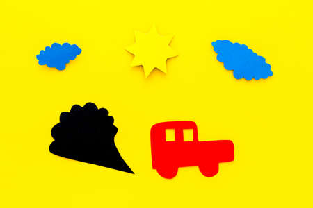 Cars emitting carbon dioxide. Pollution concept. harm the environment. Car and smoke cutout on yellow background top view.