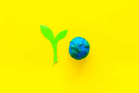 Planet, ecology. Plasticine symbol of planet Earth globe and plant cutout on yellow background top view. Banco de Imagens