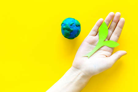 Planet, ecology. Plasticine symbol of planet Earth globe and plant cutout on yellow background top view. Stock fotó
