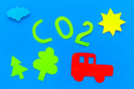 Car pollutes the environment by carbon dioxide. Car, environment and CO2 cutout on blue background top view.