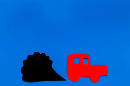 Car emitting dirty smoke. Pollution concept. Car and smoke cutout on blue background top view. Stock Photo