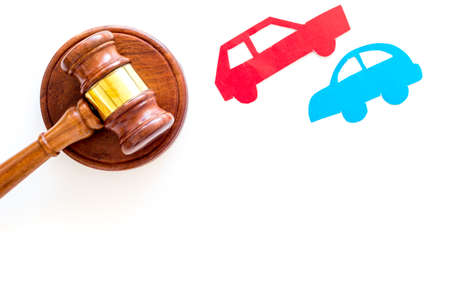 Car accident lawsuit concept. Two collided cars near judge gavel on white background top view.