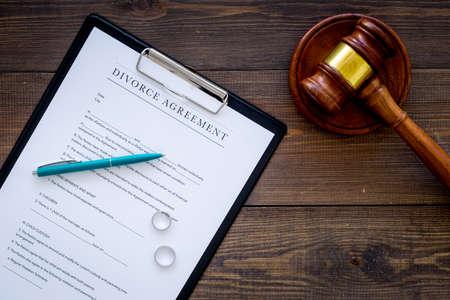 Divorce court case. Divorce agreement near wedding rings and judge gavel on dark wooden background top view. Stock Photo
