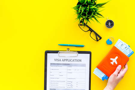 Planning vacation. Visa processing. Hand hold airplane tickets in passport cover with airplane silhouette near visa application form, compass on yellow background top view. Archivio Fotografico - 104492412