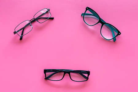 Glasses concept. Set of glasses with different eyeglass frame and transparent lenses on pink background top view. Stock Photo