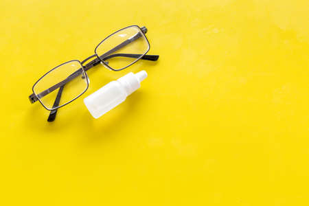 Eye drops in small bottle near glasses on yellow background top view. Stock Photo