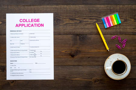 Apply college. Empty college application form near coffee cup and stationery on dark wooden background top view. 스톡 콘텐츠