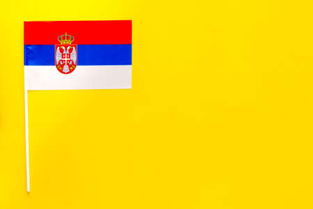 Serbian flag concept. small flag on yellow background top view copy space